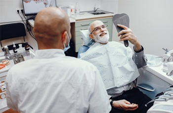 An older man laying back in a dentist chair smiling at himself in the mirror