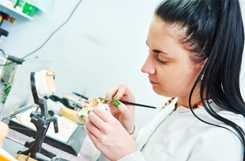 A dental lab technician working on a prosthetic