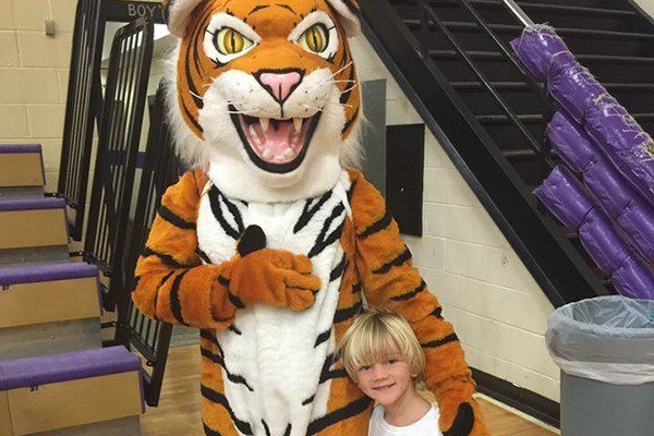 Child posing with tiger mascot