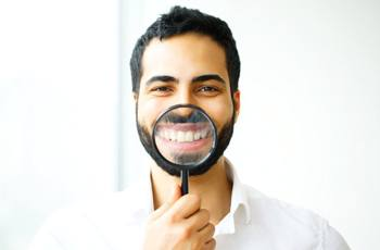 man smiling through magnifying glass