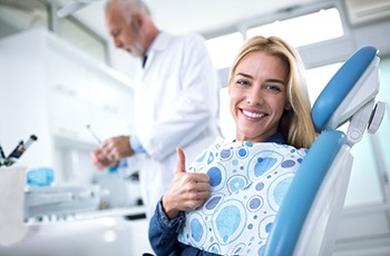 woman giving thumbs up in the dental chair