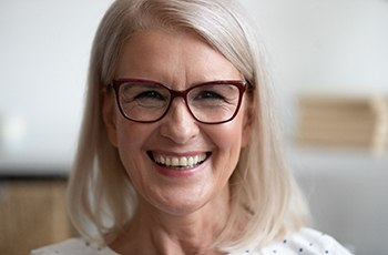 mature woman with glasses smiling