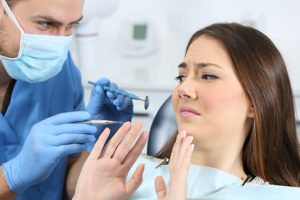 Womin in dental chair talking to dentist