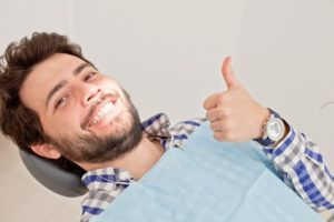 Man with thumbs up in dentist's chair