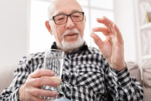 person holding a water glass and a pill