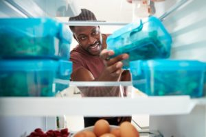 person taking food out of their refrigerator