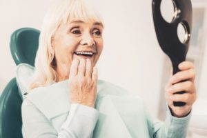 happy senior woman admiring new teeth in mirror