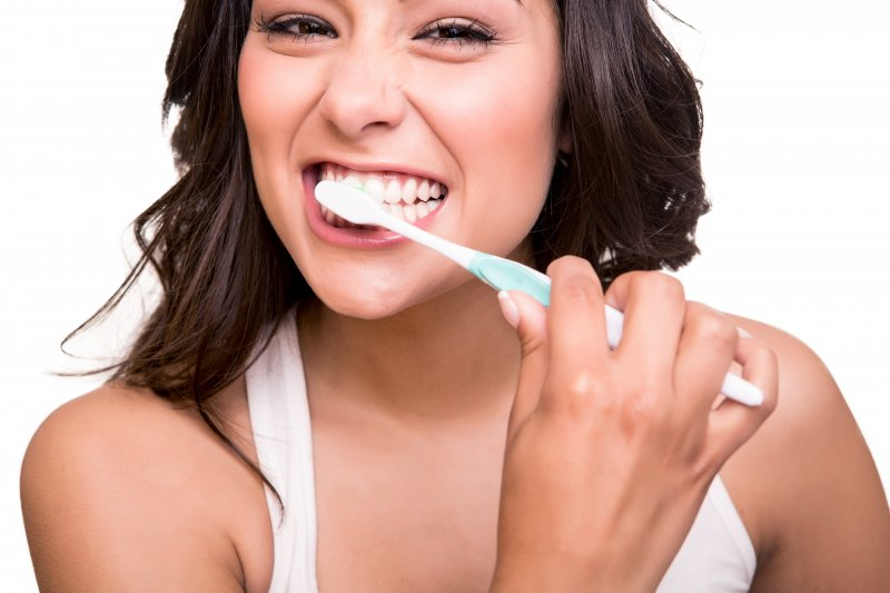 woman brushing teeth as instructed by family dentist in Columbia