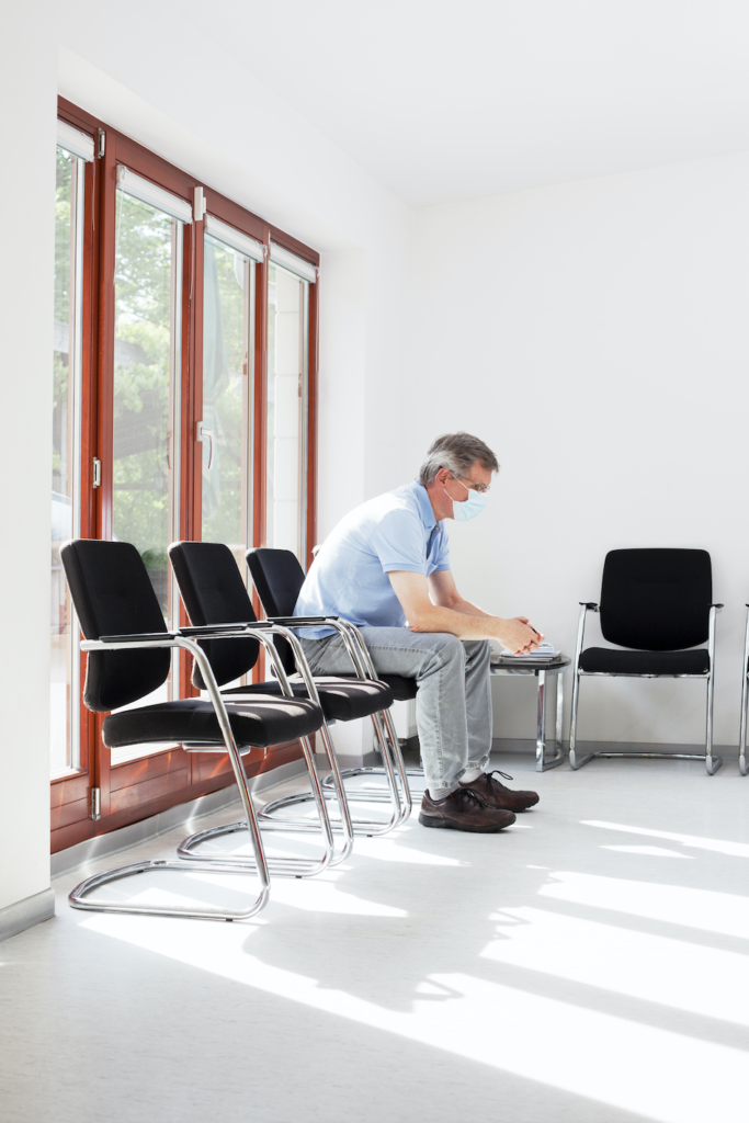 Man practicing social distancing in waiting room