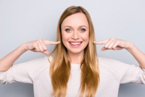 Woman points to her healthy smile after visiting Columbia cosmetic dentist