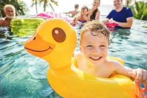 Boy with innertube in pool smiles after seeing his Columbia dentist