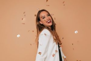 Woman wearing a white blazer smiling with gold confetti raining over her